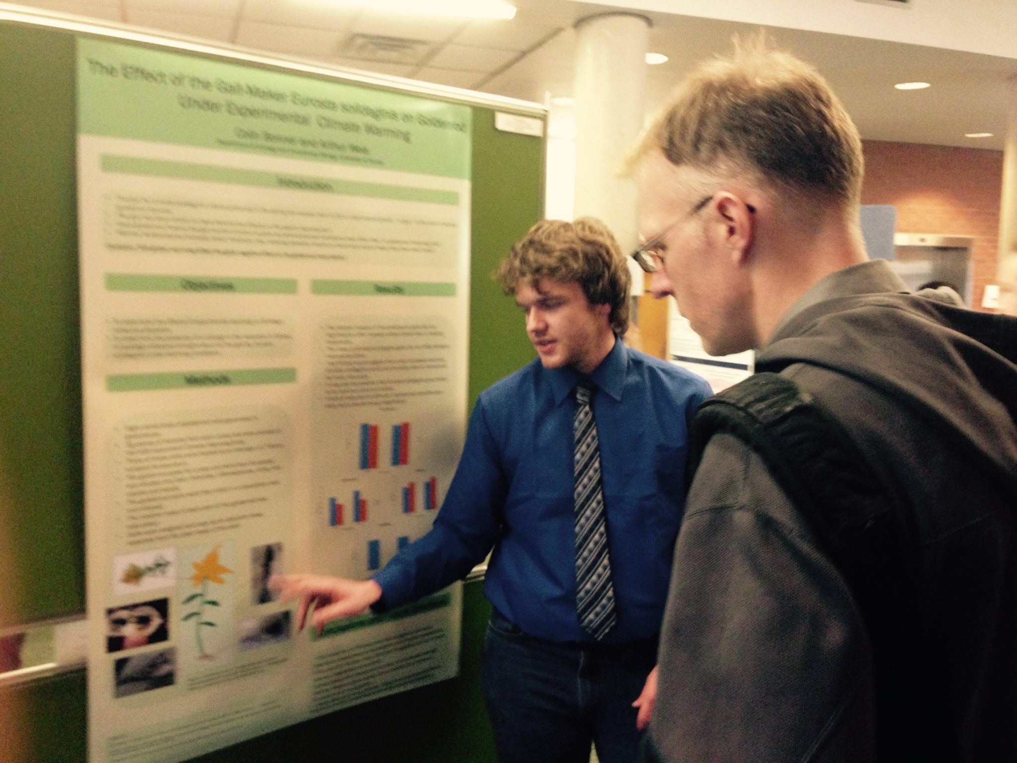 Colin Bonner explain his 2014 undergraduate research poster to Ben Gilbert.